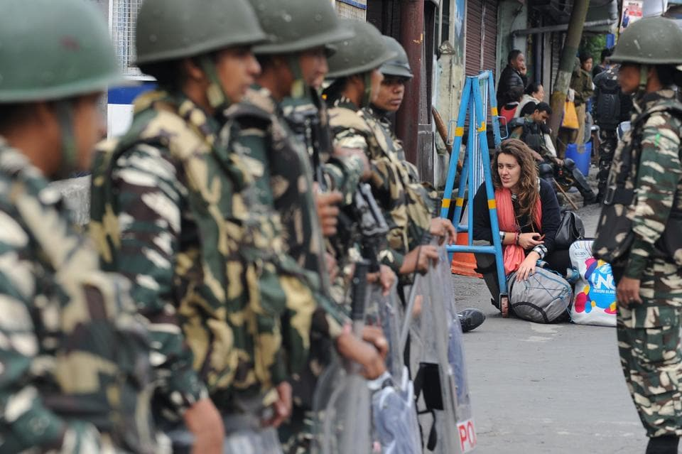 An international tourist sits on the road as Indian paramilitary troops stand guard in Darjeeling on June 18, 2017, following a day of clashes with supporters of the separatist Gorkha Janmukti Morcha (GJM) group. Hundreds of protesters on June 18 paraded with coffins containing the bodies of two men they claimed were killed in clashes with Indian security forces in Darjeeling, as the hill resort reels from separatist unrest. / AFP PHOTO / DIPTENDU DUTTA (AFP)