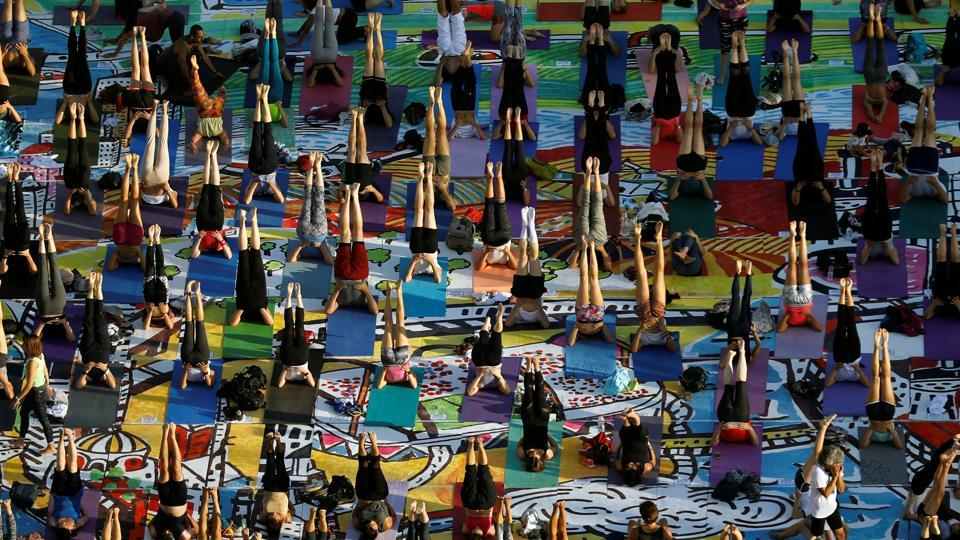 People practice yoga on 1500 yoga mats, printed with an artwork and placed together to form the artwork, during an event marking International Yoga Day, at Rabin Square in Tel Aviv, Israel June 21, 2017. REUTERS/Amir Cohen