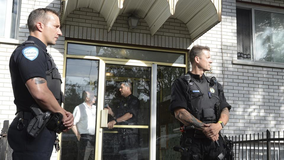 Police stand guard in front of an apartment building in Montreal, Wednesday, June 21, 2017.