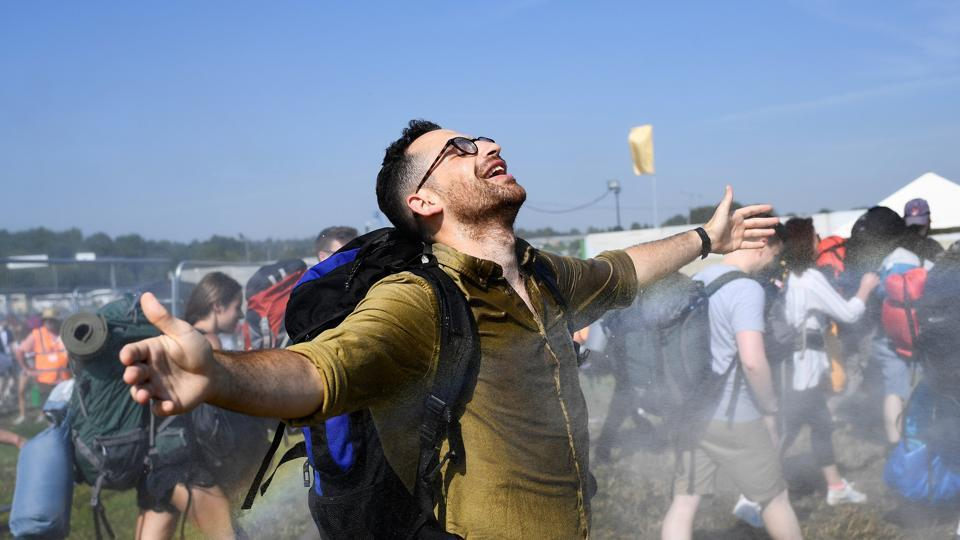 Festival goers are sprayed with water as they cool down at Worthy Farm in Somerset. (REUTERS)