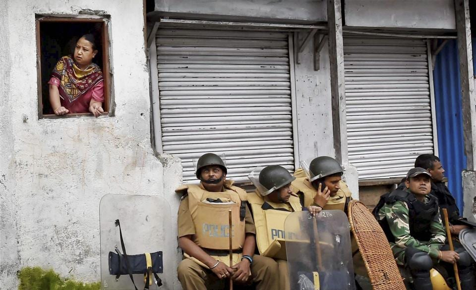 Security personnel sit guard as a woman looks out of a window in Darjeeling, West Bengal. As the Gorkha Janmukti Morcha (GJM) indefinite strike completes a week, normal life continues to suffer amid protests, calls for the separate state of Gorkhaland still ringing and the deployment of paramilitary personnel in the hill town. While an all-party meet is scheduled on June 22, 2017 to address the unrest, chief minister Mamata Banerjee's announced absence has opposition parties unsure about the impact of the gesture.  (Ashok Bhaumik/PTI)
