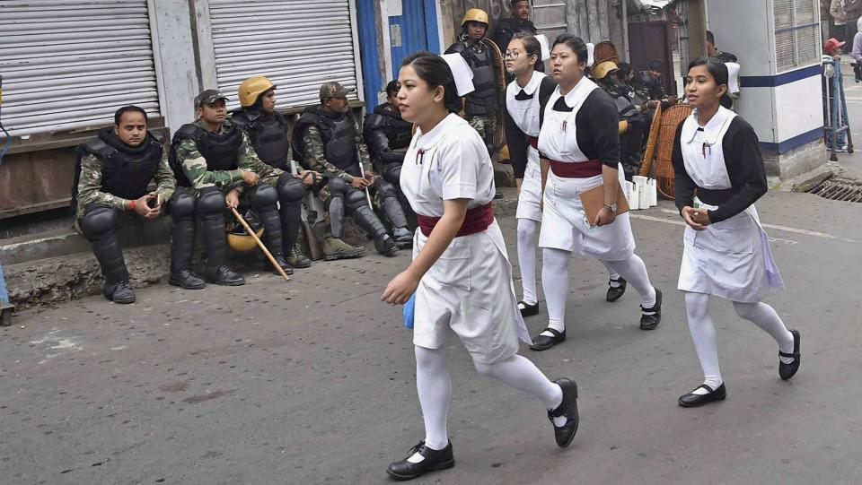 Darjeeling: Nurses walk past security forces personnel guarding in a street during Gorkha Janamukti Morcha's indefinite strike in Darjeeling on Monday. PTI Photo by Ashok Bhaumik (PTI6_19_2017_000131A) (PTI)