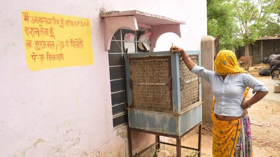 A woman stands near the official writing on the wall outside her home in Pilodi in Dausa.