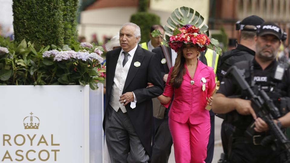 Innes Hernandes, wears an ornate hat as she walks past armed policemen as she arrives on the third day of the Royal Ascot horse race. (Alastair Grant / AP)