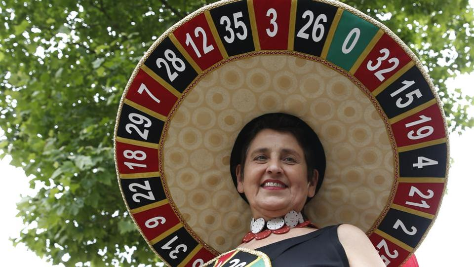 A racegoer wears a hat based on a roulette wheel. (Alastair Grant / AP)