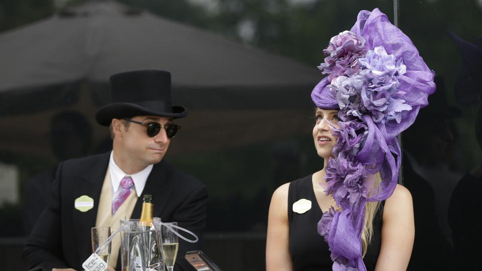 A pretty racegoer poses in a black strappy dress and her giant purple flowers headwear. (AP)