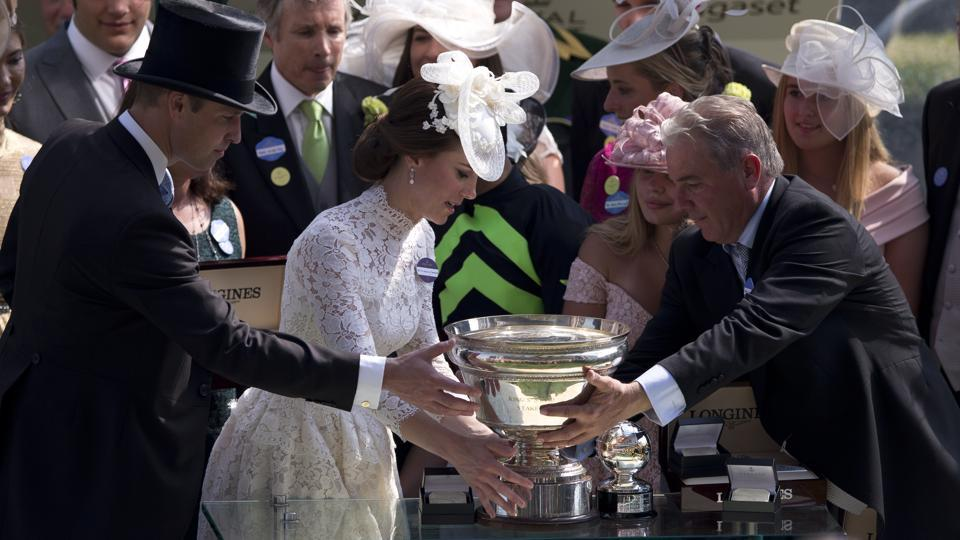 Britain's Prince William, left, and Kate, the Duchess of Cambridge present the trophy for the King's Stand Stakes to the Wesley A. Ward trainer of the winning horse Lady Aurelia of the United States, ridden by John Velazquez, in the parade ring on the first day o the Royal Ascot horse race meeting in Ascot, England. (Alastair Grant / AP)