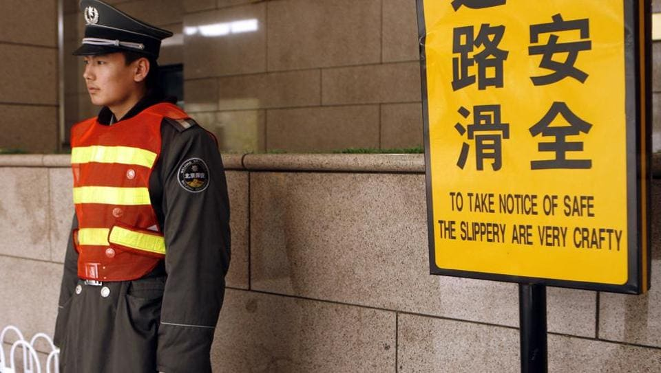File photo from April 2007 shows a security guard standing next to a sign which reads in English