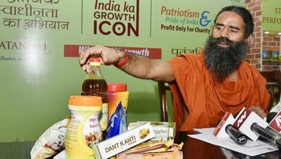 "Ramdev shows ""Patanjali"" products before addressing a press conference in New Delhi."