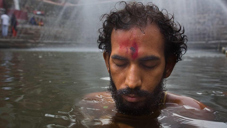 An Indian devotee prays as he takes a dip in Saubhagya Kunda, a holy pond at Kamakhya temple during the Ambubachi festival.  (AP)