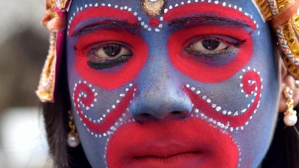 A portrait of an Indian devotee dressed as the Hindu deity Kali attends the Kamakhya Temple  (AFP)