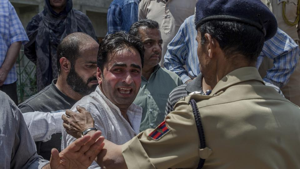 A police officer comforts a wailing relative of Mohammad Ayoub Pandith, a policeman who was beaten to death, during a wreath laying ceremony at the police headquarters in Srinagar.