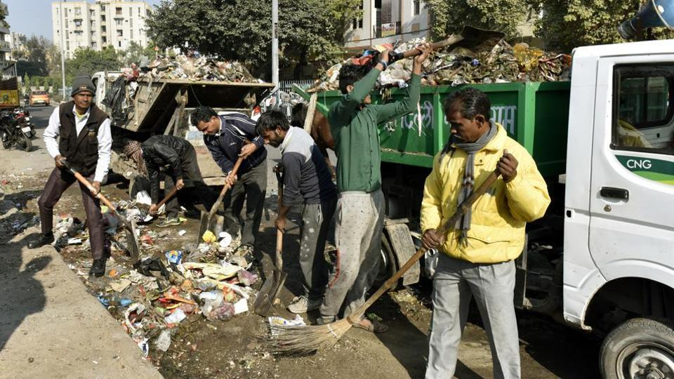 The East Delhi Municipal Corporation workers remove garbage at Chilla Village near Mayur Vihar.