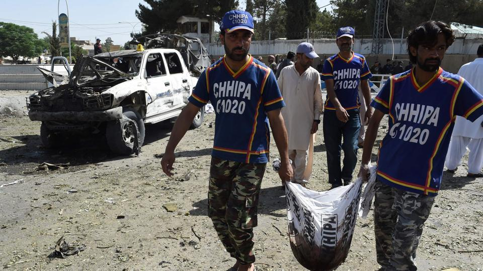 Pakistani volunteers move the remains of a victim at the site of a suicide attack that targeted police in Quetta on June 23, 2017.
