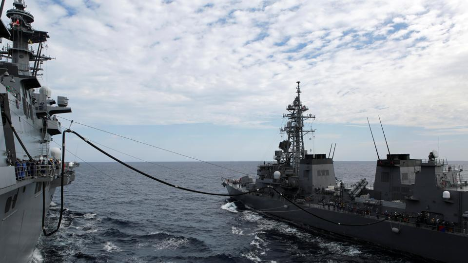 Japan Maritime Self-Defense Force (JMSDF) helicopter carrier Izumo (L) receives fuel replenishment from JMSDF Takanami class destroyer Sazanami during a military exercise in South China Sea, near Singapore, June 20, 2017.