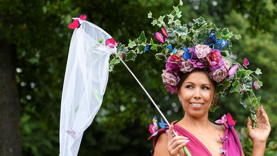 A racegoer wearing a hot pink ornate dress that was adorned with a garden-inspired hat (Toby Melville / Reuters)