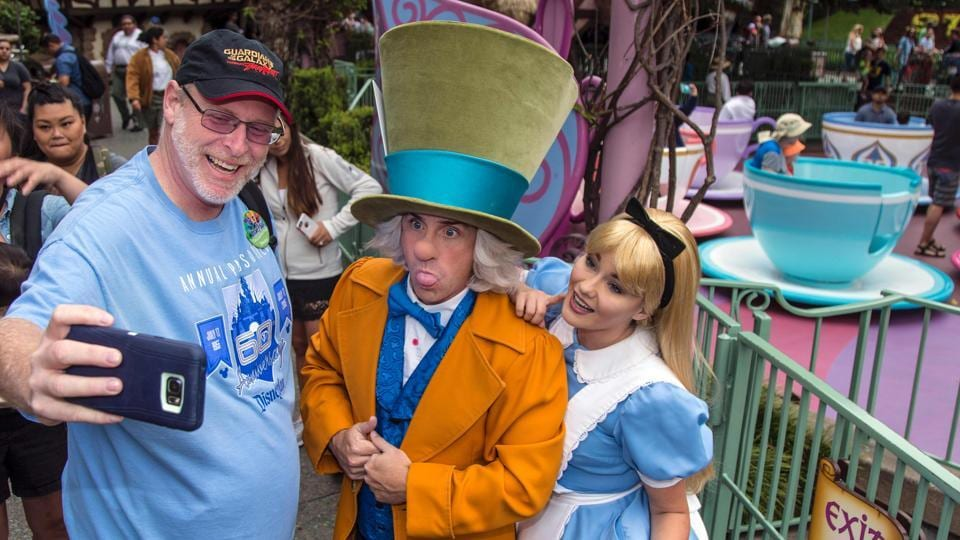 Jeff Reitz clicks a selfie with the Mad Hatter and Alice after a teacup ride at the Mad Tea Party in Fantasyland at Disneyland on June 22, 2017, during his 2,000th visit to the park in Anaheim, California.