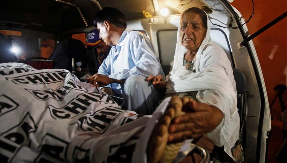 A mother of a policeman, who was killed along with three of his companions in a gun attack, touches the feet of her son while transporting his body in an ambulance outside a hospital morgue in Karachi, Pakistan June 23, 2017.