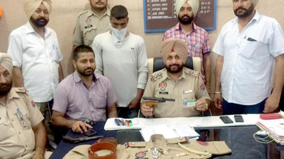 Chabhal station house officer (SHO) Harchand Singh (centre) with the imposter  (face covered) ,who was posing as assistant sub-inspector (ASI), at Chabhal in Tarn Taran district on Saturday.
