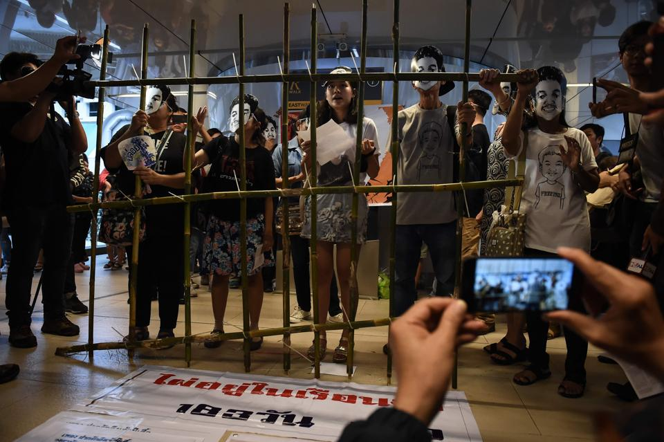 """People stand behind makeshift bars wearing masks of Thai human rights activist Jatupat """"Pai"""" Boonpattararaksa, who was arrested in early December 2016 and charged with lese majeste for sharing a profile of King Maha Vajiralongkorn written by the BBC's Thai-language service, during a demonstration marking Jatupat's sixth month in detainment, in Bangkok on June 22, 2017."""