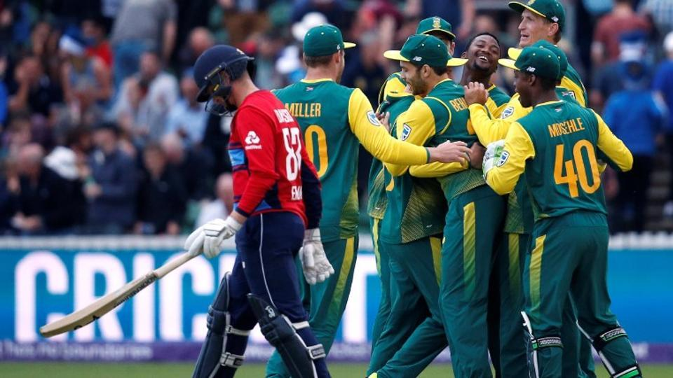 South Africa players celebrate their win as England's Liam Dawson looks on.