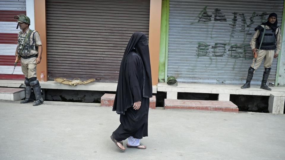 A woman walks past shops during a curfew in Srinagar on Friday, a day after Mohammad Ayub Pandith was beaten to death at Jama mosque.