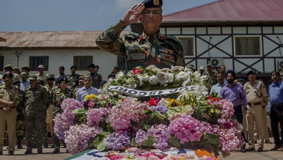 An Indian army officer salutes during the wreath-laying ceremony of Mohammad Ayoub Pandit, a policeman who was beaten to death, at the police headquarters in Srinagar, Friday, June 23, 2017.