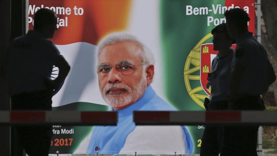Police stand by a welcome poster showing Prime Minister Narendra Modi at the entrance of the Necessidades Palace, the Portuguese Foreign Ministry in Lisbon, Portugal.