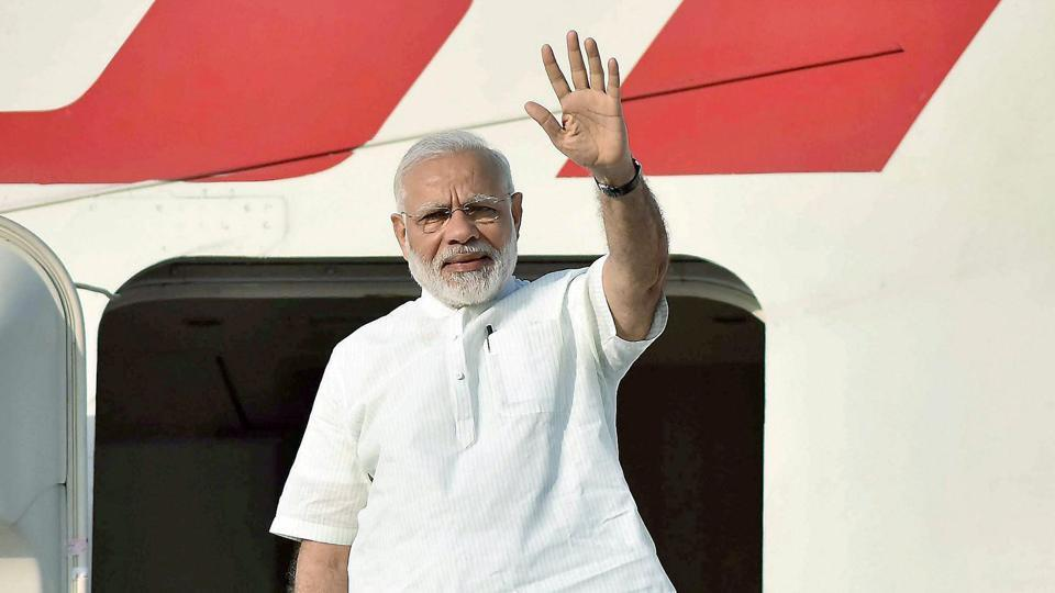 Prime Minister Narendra Modi waves as he emplanes in New Delhi on Saturday for his visit to Portugal, the US and the Netherlands.