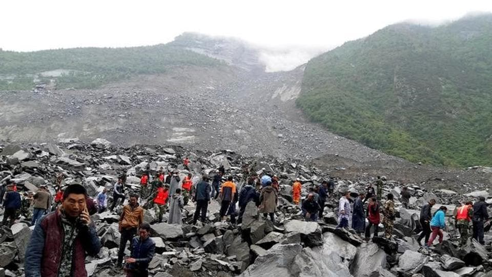 People search for survivors at the site of a landslide that destroyed some 40 households, where more than 100 people are feared to be buried in Xinmo village in Sichuan province.