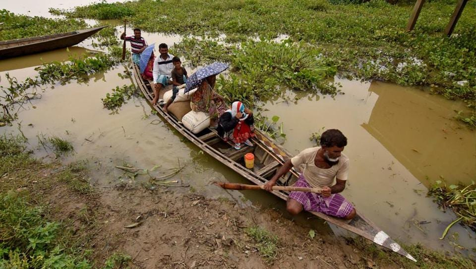 People are transported in a boat to a safer place in a flooded wetland at Balimukh village in Morigaon district, Assam, on June 18, 2017.