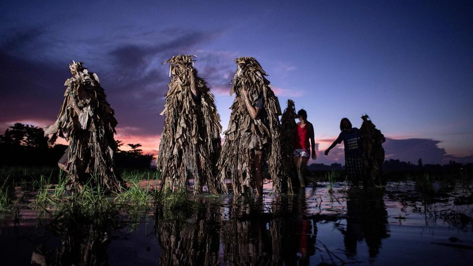 At dawn every June 24th, people from Bibiclat village in Nueva Ecija pay homage to their patron saint, John the Baptist, by gathering in silence in a swampy field to cover themselves in mud. (Noel Celis / AFP)
