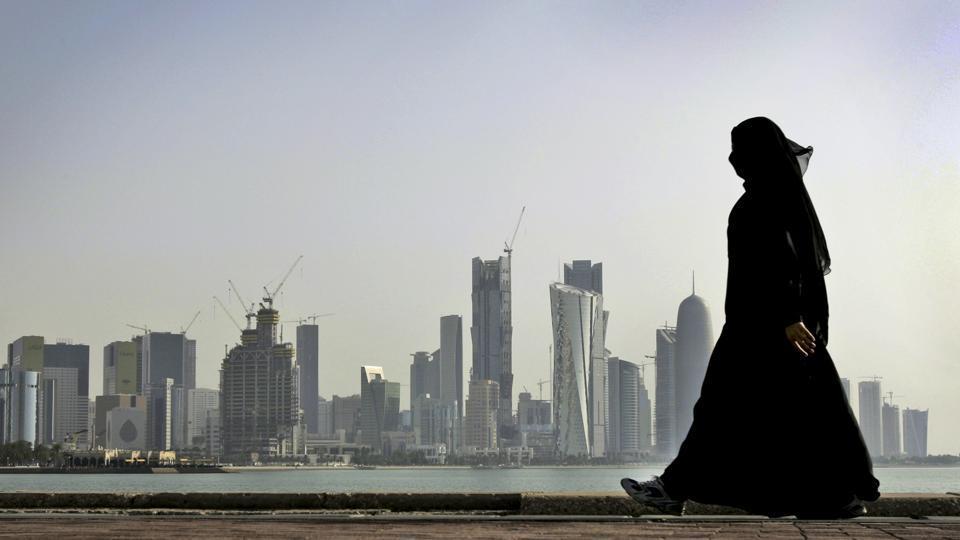 A Qatari woman walks in front of the city skyline in Doha, Qatar.