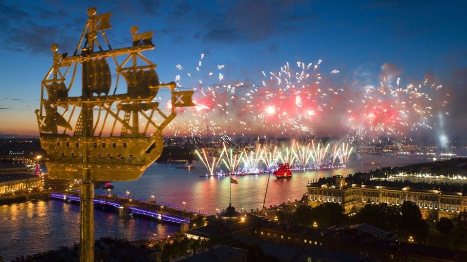 An aerial view of light show and firework with a brig with scarlet sails, right, floating on the Neva River . The city landmark, weathercock in the form of a ship fixed atop a spire of the Admiralty building is in the foreground. (Dmitri Lovetsky / AP)