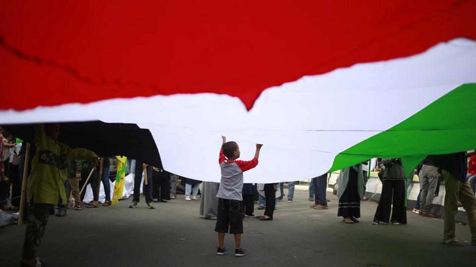 A boy plays under a large Palestinian flag during a pro-Palestinian rally marking the International Al-Quds (Jerusalem) Day outside the U.S. Embassy in Jakarta, Indonesia, Friday on June 23, 2017. Al-Quds Day, which was declared by the late Iranian spiritual leader Ayatollah Ruhollah Khomeini in 1979 as an international day of struggle against Israel and for the liberation of Jerusalem, is observed every last Friday of the Muslim holy month of Ramadan. (Dita Alangkara/AP)
