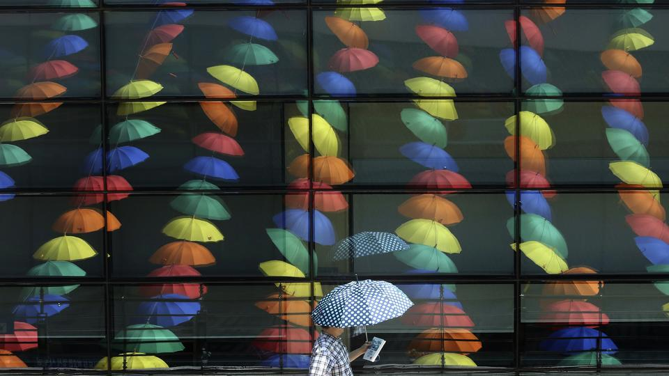 A man walks by window reflections of sun umbrellas used in an art display in a courtyard at the Geumcheon government building in Seoul, South Korea,  on June 22, 2017. During past several days, the temperature soared over 30 degrees Celsius (86 degrees Fahrenheit), in afternoon, bringing a steamy heat to the capital area, according to weathermen.  (Ahn Young-joon/AP)