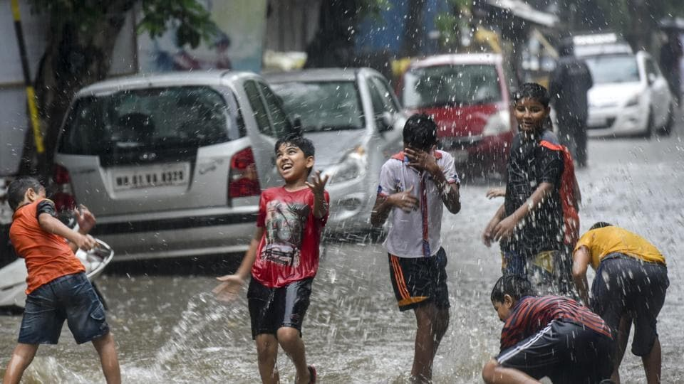 Children play in a waterlogged street after heavy rainfall at Hindamata on Sunday.