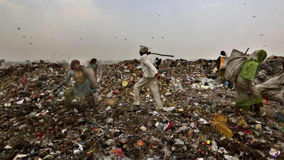 An MCD worker chases away ragpickers with a stick at the Ghazipur landfill site in east Delhi.