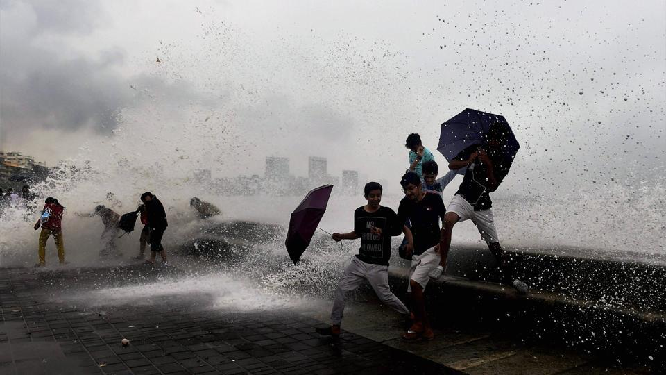 People enjoy a high tide at the Marine Drive promenade following the heavy showers in Mumbai on Sunday.