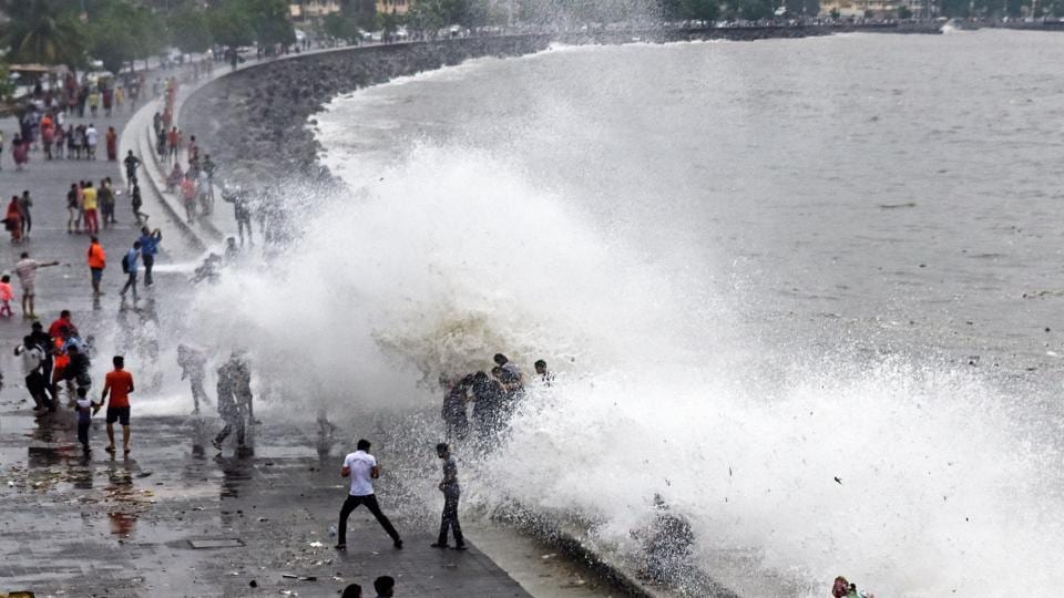 Locals feel the cool spray of seawater during high tide on Sunday. (Pratik Chorge/HT)