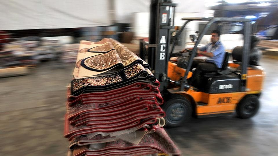 An employee transfers carpets from one section to another at a factory in Bari Brahmana industrial area on Sunday. (Nitin Kanotra/HT Photo)