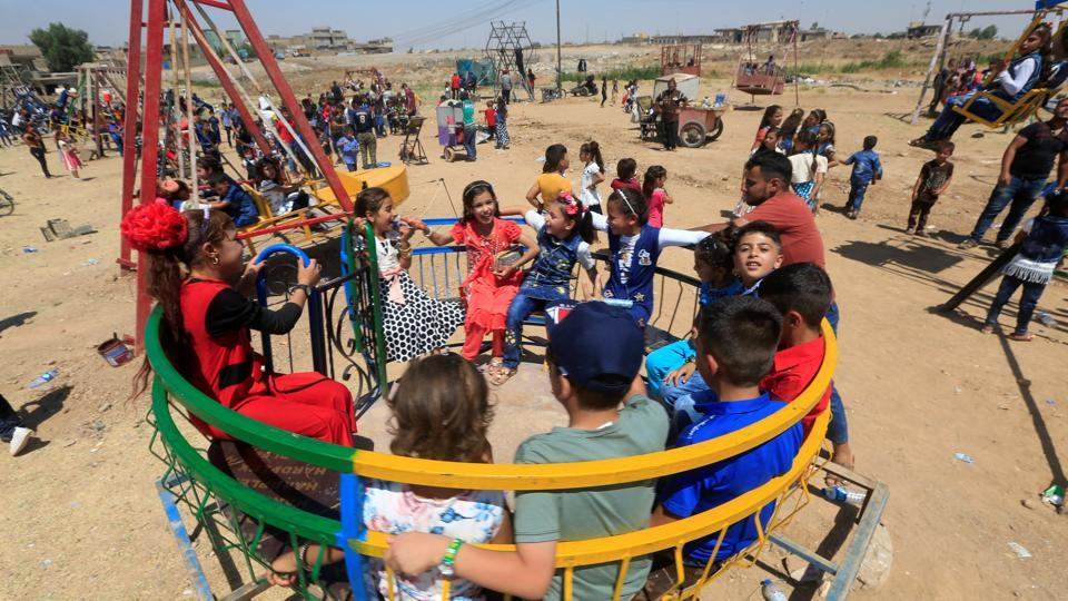 Iraqi children play as they celebrate Eid al-Fitr, in Mosul, Iraq on Sunday.