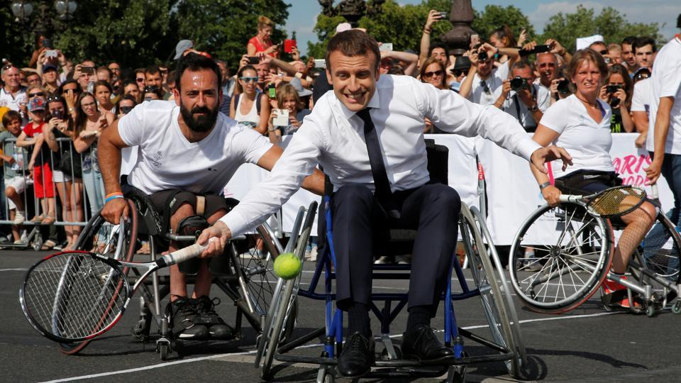 French President Emmanuel Macron returns the ball while sitting in a wheelchair as he plays tennis on the Pont Alexandre III in Paris, France on June 24, 2017. The French capital is transformed into a giant Olympic park to celebrate International Olympic Days with a variety of sporting events for the public across the city during two days as the city bids to host the 2024 Olympic and Paralympic Games.  (Jean-Paul Pelissier/REUTERS)