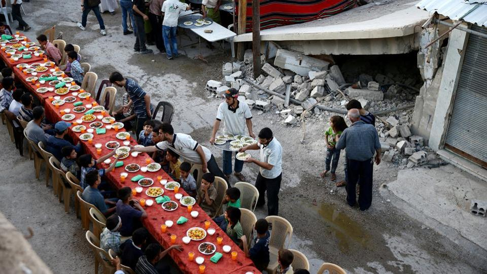 People gather for Iftar (breaking fast), organised by Adaleh Foundation, amid damaged buildings during the holy month of Ramadan in the rebel-held besieged town of Douma to the east of Damascus, Syria on June 18, 2017.  (Bassam Khabieh/REUTERS)