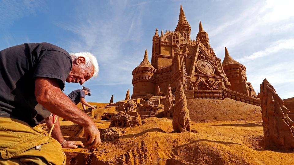Sand carver Franco Daga from Italy works on a sculpture during the Sand Sculpture Festival