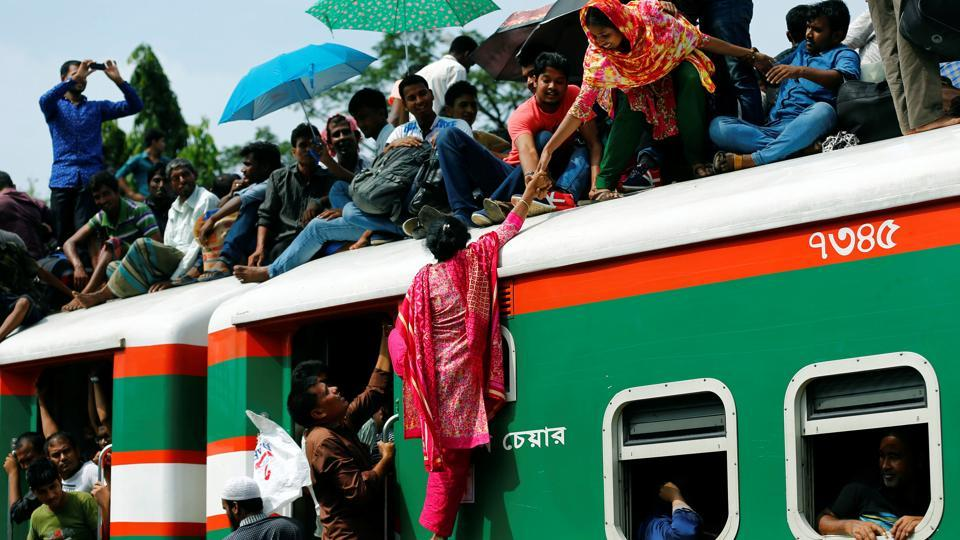 A woman helps another woman to get atop of an overcrowded passenger train as they travel home to celebrate Eid al-Fitr festival at a railway station in Dhaka, Bangladesh on June 23, 2017.  (Mohammad Ponir Hossain/REUTERS)
