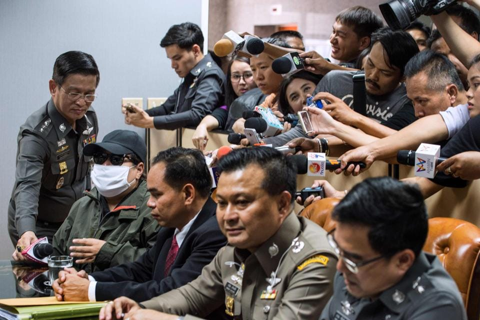This picture taken on April 25, 2017 shows the mother of a victim of a sex trafficking ring (2nd L) surrounded by members of the media as she meets with Thai police officials during an inquiry at the police headquarters office in Bangkok.