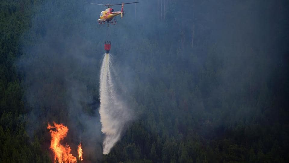A helicopter drops water over a wildfire in Carvalho, next to Pampilhosa da Serra, on June 19, 2017. More than 1,000 firefighters are still trying to control the huge forest fire that erupted on June 17, 2017 in central Portugal killing at least 62 people and injuring 62 more, many trapped in their cars by the flames, causing a great deal of emotion in the country.  (Miguel Riopa/AFP)