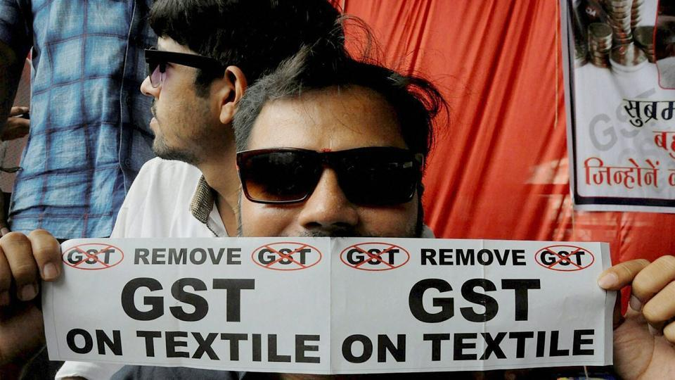 A man brandishes a poster with an anti-GST message printed on it, during a sit-in by traders protesting the soon-to-be-implemented tax regime, in Surat.