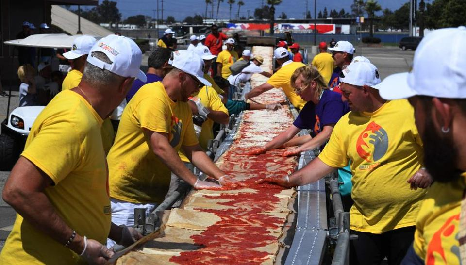 Volunteers spread tomato sauce and cheese onto the pizza base as they successfully break the Guinness World Record for the longest pizza in Fontana, California.